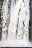 Frau, die vor gigantischem Skogafoss-Wasserfall in Island steht lizenzfreie stockfotos
