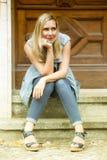 Frau, die vor Holztür auf Schritten sitzt Lizenzfreie Stockfotografie