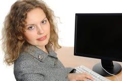 Frau, die vor ihrem Computer lächelt Lizenzfreie Stockfotografie