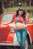 Frau, die vor Retro- rotem Auto steht Stockfotografie
