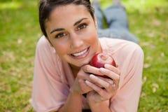 Frau, die voran beim Anhalten eines Apfels schaut Lizenzfreies Stockfoto