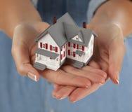 Frau, die vorbildliches Haus in den Händen anhält Lizenzfreies Stockfoto