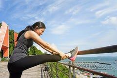 Frau, die vorher ihr Bein bevor dem Laufen ausdehnt Stockbilder