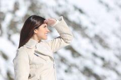 Frau, die vorwärts mit der Hand auf Stirn im Winter schaut Stockfotografie