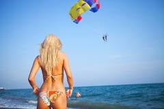 Frau, die vorwärts zu einem Gleitschirmfliegenabenteuer schaut Lizenzfreie Stockfotografie