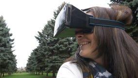 Frau, die an vr Kopfhörer setzt und um im Freien in einer Welt der virtuellen Realität schaut stock footage