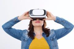 Frau, die VR-Kopfhörer trägt und oben im Isolat der virtuellen Realität auf weißem Hintergrund schaut moderner Laptop getrennt au Stockfotos