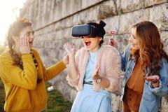 Frau, die VR-Kopfhörergläser 360, VR-Erfahrung im Freien verwendet Sichtwirklichkeitskonzept Aufgeregtes Erfahren mit drei Mädche stockfoto