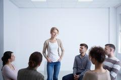 Frau, die während der Gruppentherapie spricht stockfotografie
