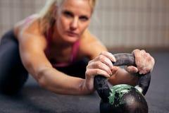 Frau, die während des Kettlebell Trainings stillsteht Lizenzfreies Stockbild