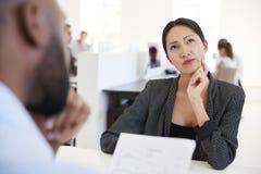 Frau, die während eines Vorstellungsgesprächs in einem Bürogroßraum denkt lizenzfreies stockfoto