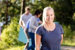 Frau, die während Freunde machen Pyramide von den Planken im Wald lächelt Lizenzfreies Stockfoto