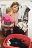 Frau, die Wäscherei tut und Tochter anhält lizenzfreies stockfoto
