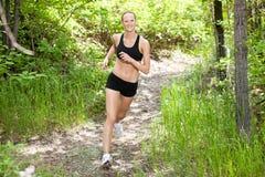 Frau, die in Wald lächelt und läuft Lizenzfreies Stockfoto
