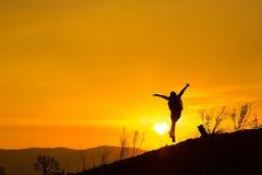 Frau, die wandert, um den Sonnenuntergang aufzupassen Schattenbild, Springen froh stockfotografie