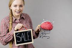 Frau, die Warenkorb mit Gehirn und Verkauf hält Stockbilder