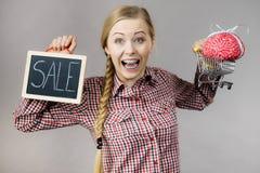 Frau, die Warenkorb mit Gehirn und Verkauf hält Lizenzfreies Stockbild