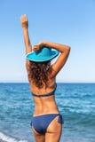 Frau, die warmen Sommertag an einer Küste genießt stockfotografie