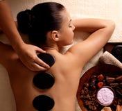 Frau, die Warmsteinmassage im Badekurortsalon erhält. Stockfoto