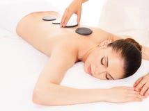 Frau, die Warmsteinmassage im Badekurortsalon hat. Lizenzfreies Stockfoto