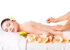 Frau, die Warmsteinmassage im Badekurortsalon hat. Stockbilder