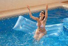 Frau, die Wasser über ihrem Kopf spritzt Stockfoto