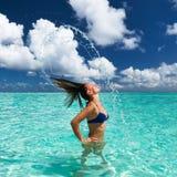 Frau, die Wasser mit dem Haar im Ozean spritzt Lizenzfreies Stockfoto
