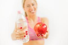 Frau, die Wasserflasche und -apfel hält Lizenzfreie Stockbilder