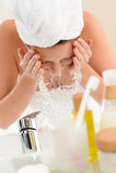 Frau, die Wassergesicht im Badezimmer spritzt Lizenzfreies Stockfoto