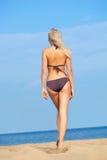 Frau, die weg auf Strand geht Lizenzfreie Stockfotografie