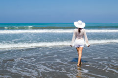 Frau, die weg dem Meer auf dem Strand betrachtet Lizenzfreie Stockbilder