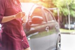 Frau, die Wegwerftasse kaffee neben Auto hält Stockfotografie