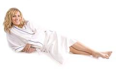 Frau, die in weiße Robe legt Lizenzfreie Stockbilder