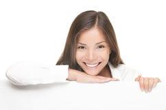 Frau, die weiße unbelegte Zeichenanschlagtafel zeigend lächelt Lizenzfreie Stockbilder