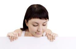 Frau, die weiße unbelegte Zeichenanschlagtafel zeigend lächelt Lizenzfreie Stockfotos