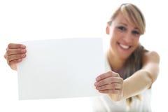 Frau, die weißes Blatt hält Lizenzfreie Stockfotografie