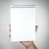 Frau, die weißes leeres Notizbuch hält Stockbild