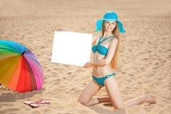Frau, die weißes leeres Plakat auf dem Strand hält Lizenzfreie Stockfotografie