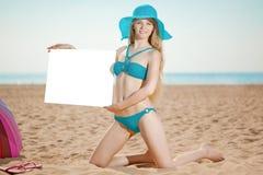 Frau, die weißes leeres Plakat auf dem Strand hält Lizenzfreies Stockbild
