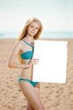Frau, die weißes leeres Plakat auf dem Strand hält Stockfoto