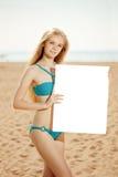 Frau, die weißes leeres Plakat auf dem Strand hält Stockfotos