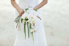 Frau, die weißen Orchideenhochzeitsblumenstrauß mit Strandhintergrund hält Stockbilder
