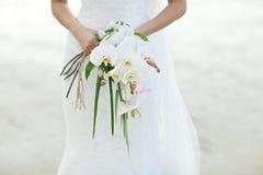 Frau, die weißen Orchideenhochzeitsblumenstrauß mit Strandhintergrund hält Lizenzfreie Stockfotos
