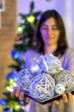 Frau, die Weihnachtsball über Lichthintergrund hält lizenzfreies stockbild