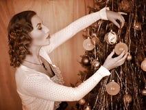Frau, die Weihnachtsbaum kleidet. Lizenzfreie Stockbilder