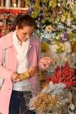 Frau, die Weihnachtsdekorationen zum Einkaufskorb setzt Stockbild
