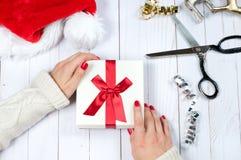 Frau, die Weihnachtsgeschenk auf einem Holztischhintergrund hält Stockfoto