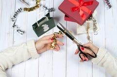 Frau, die Weihnachtsgeschenk auf einem Holztischhintergrund hält Lizenzfreie Stockbilder