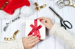 Frau, die Weihnachtsgeschenk auf einem Holztischhintergrund hält Lizenzfreies Stockfoto