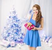Frau, die Weihnachtsgeschenk-Geschenkbox, vorbildliches Girl, blauer Baum hält Lizenzfreies Stockbild